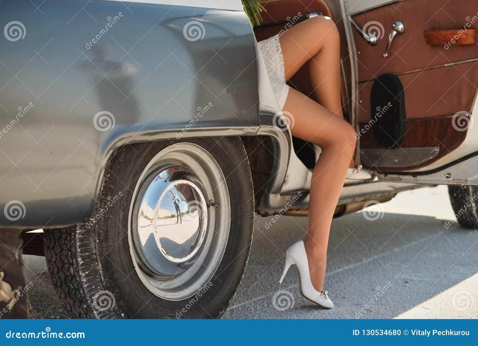 Piernas de salir de la muchacha del auto viejo mujer joven en zapatos de los tacones altos Puerta de abertura del chófer del auto