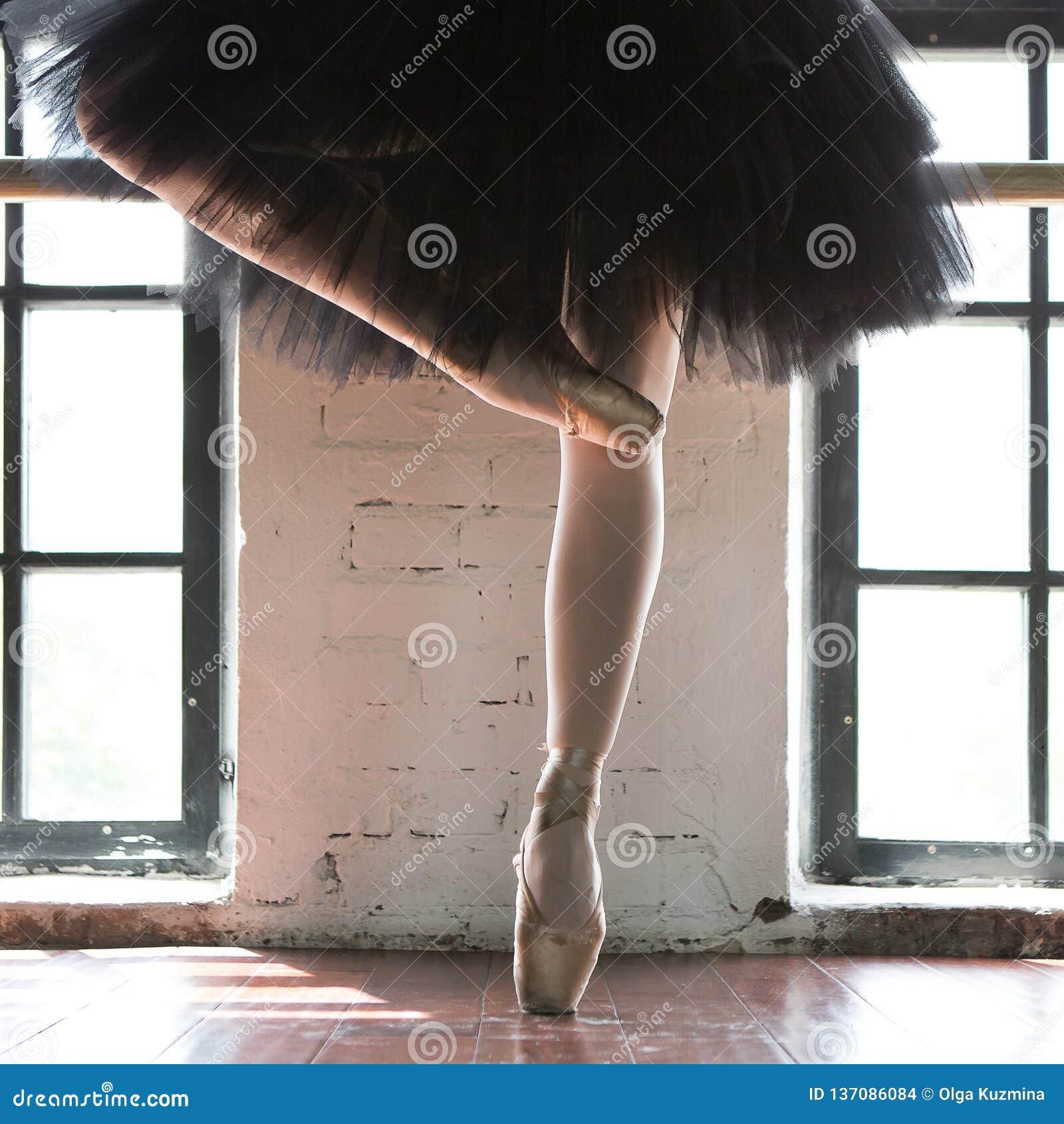 Piernas de un primer de la bailarina Las piernas de una bailarina en viejo pointe Bailarina del ensayo en el pasillo Luz del cont