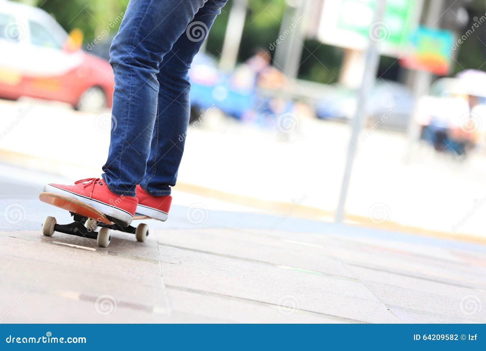 Piernas del skater que montan en el monopatín en ciudad