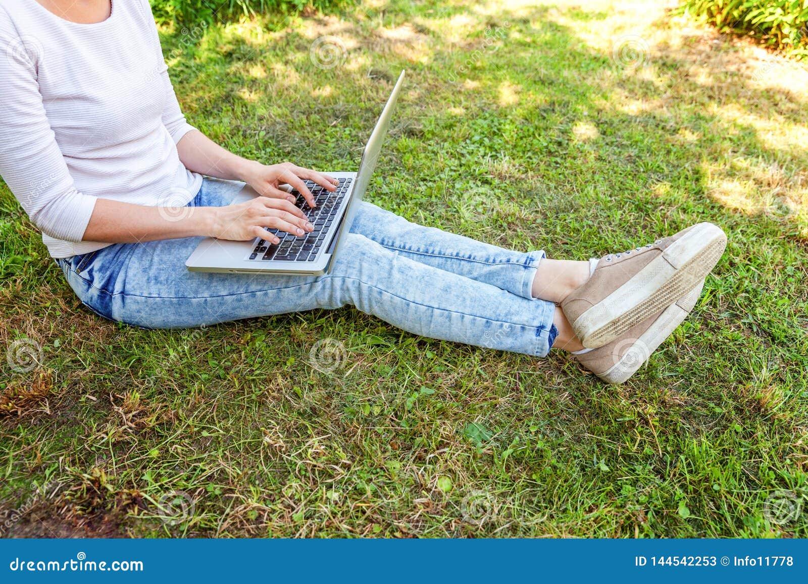 Piernas en c?sped de la hierba verde en parque de la ciudad, manos de la mujer que trabajan en el ordenador de la PC del ordenado