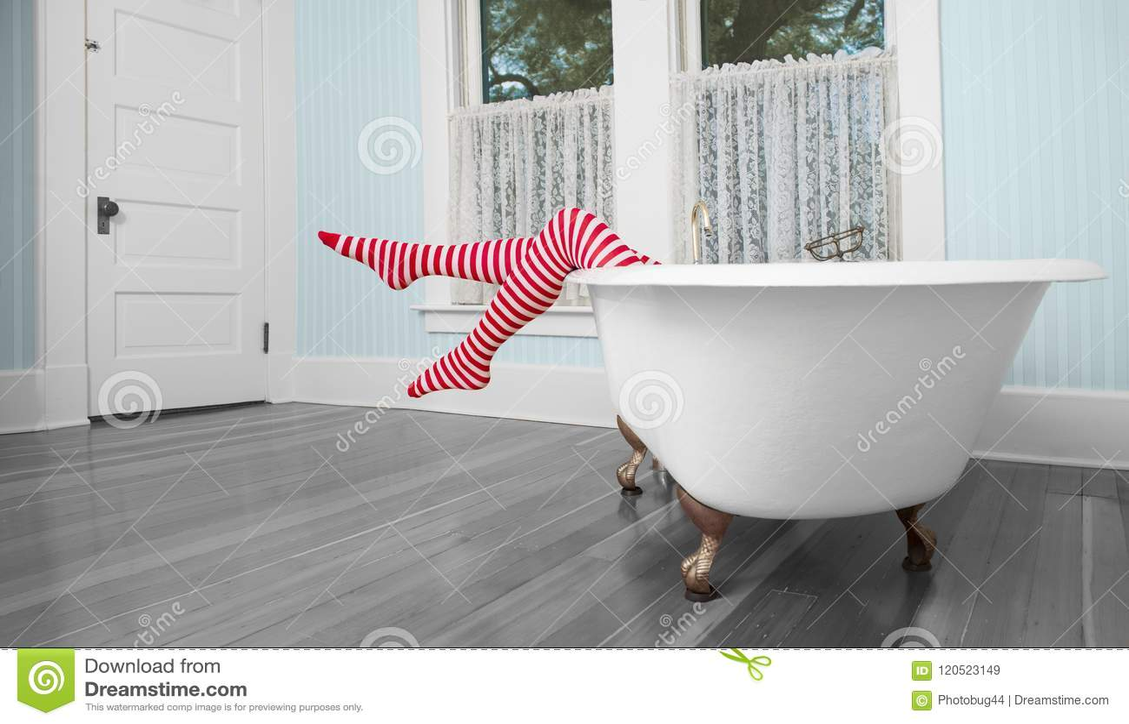 Piernas rayadas sobre la tina de baño en cuarto de baño del vintage