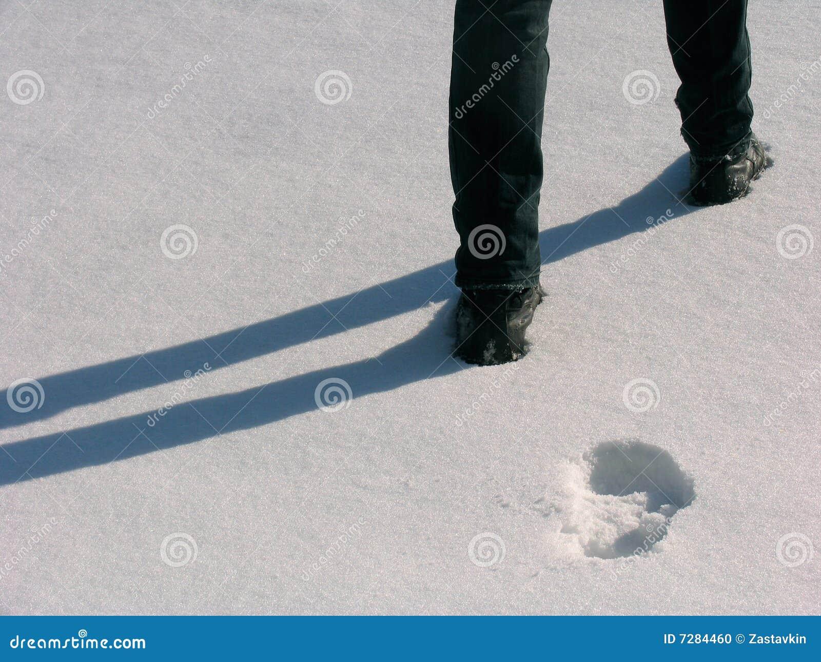 Piernas y huellas del hombre en la nieve