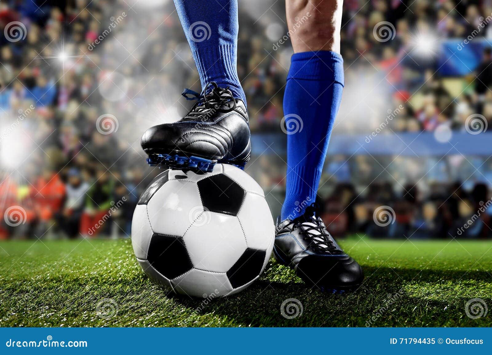 Piernas y pies del futbolista en calcetines azules y zapatos negros que se colocan con la bola que juega el partido en el estadio