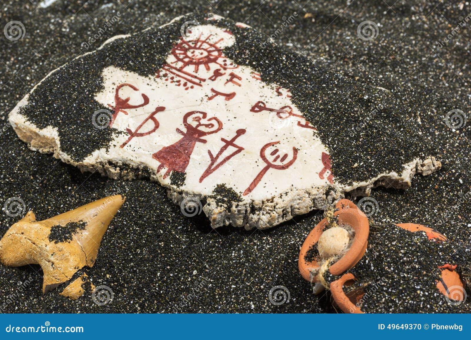 Pierre avec des pétroglyphes sur le sable