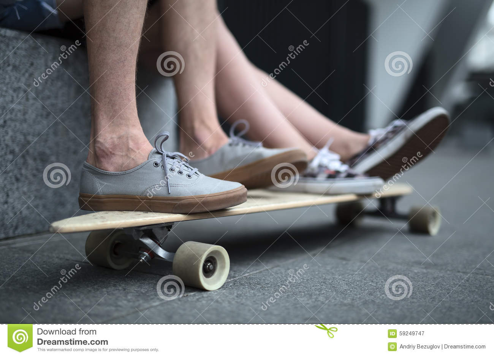 Pies de pares de adolescentes en el primer del longboard