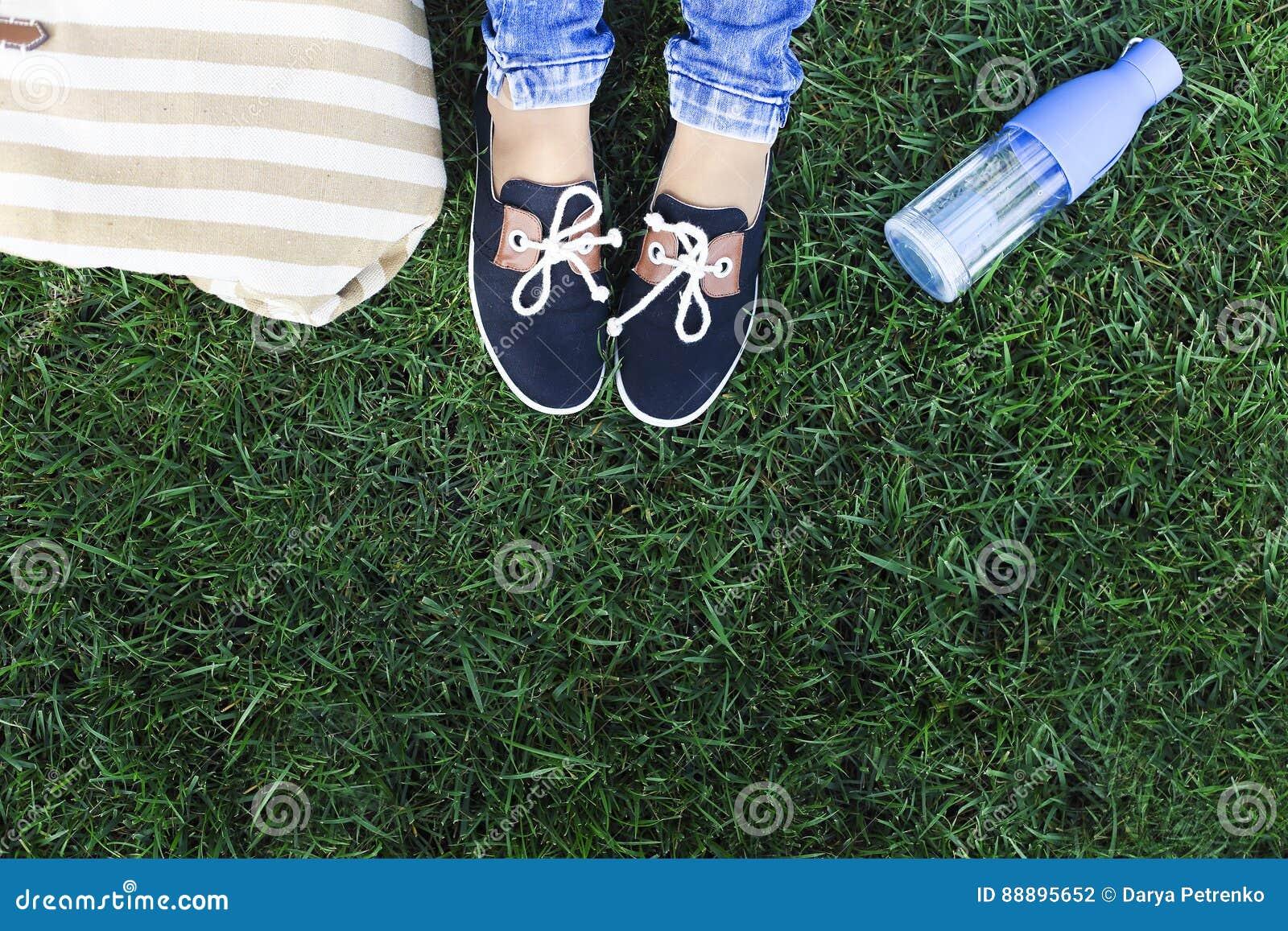 Pies de una chica joven en un fondo una hierba verde con la botella o