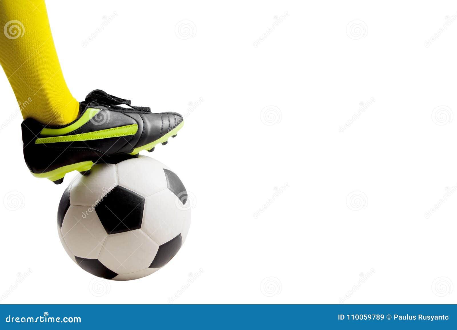 Pies del jugador de fútbol que golpean el balón de fútbol con el pie