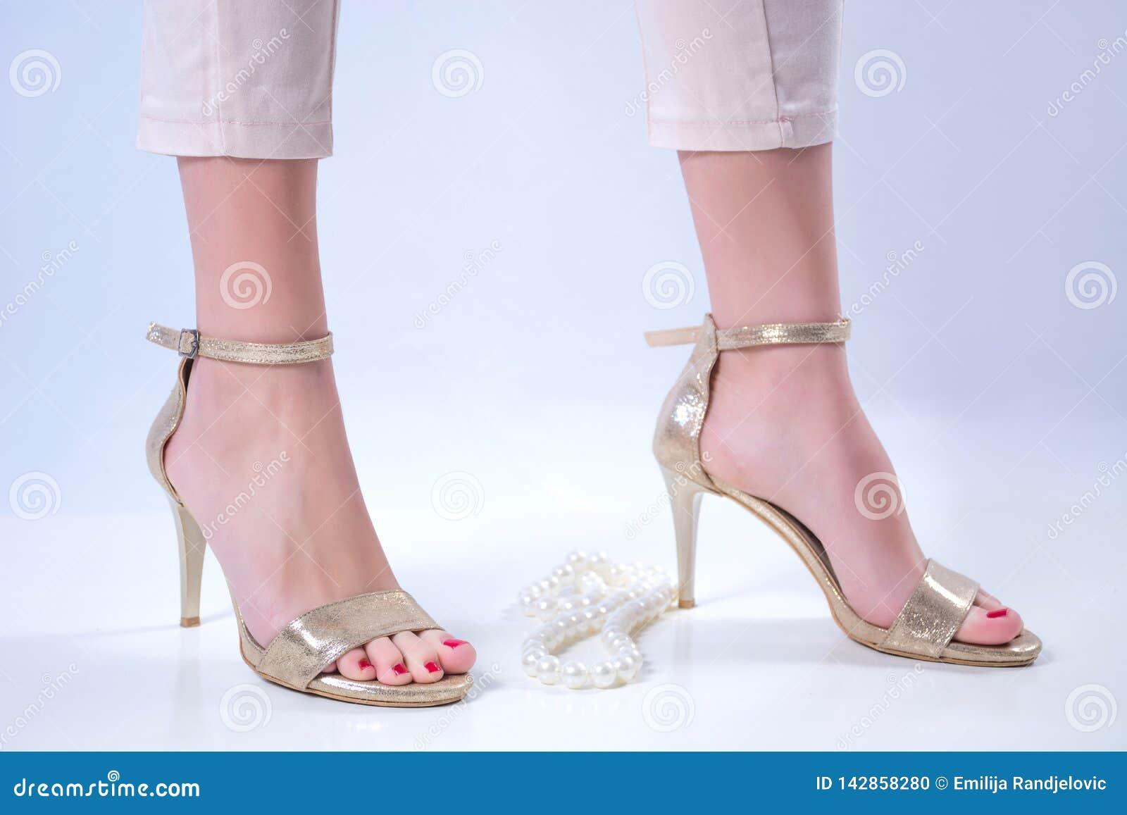 Pies desnudos de la chica joven en tacones altos y collar de oro de las perlas en el fondo blanco
