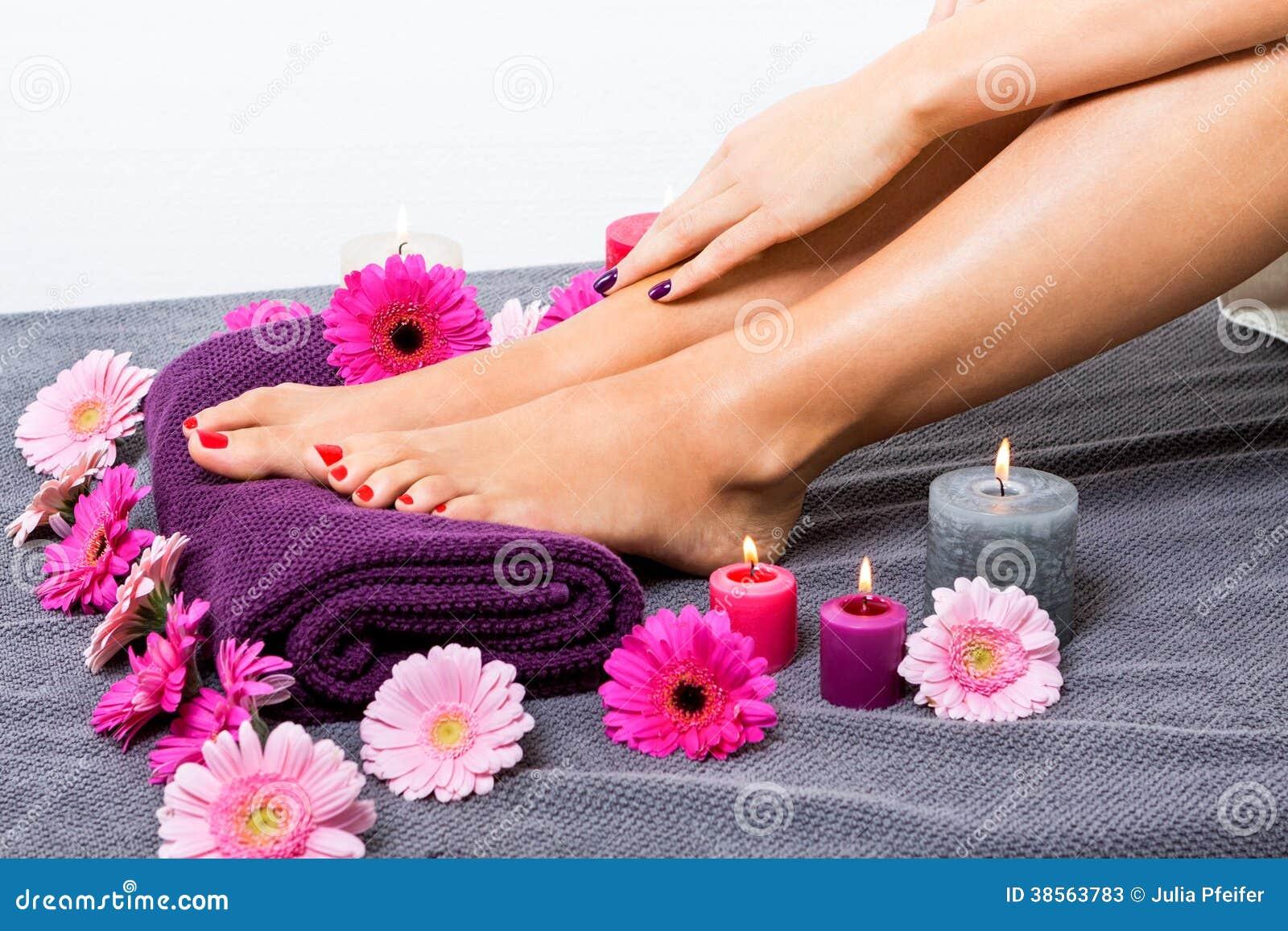 Pies desnudos de una mujer rodeada por las flores