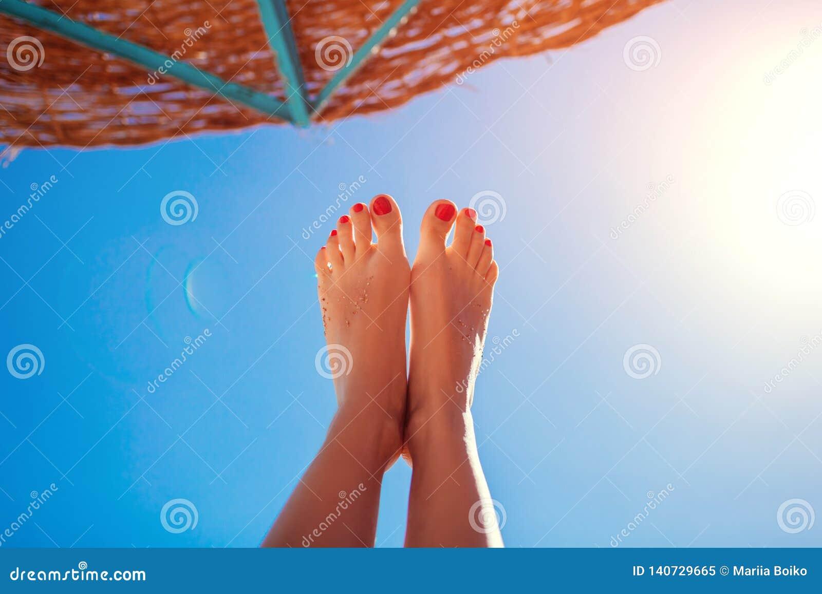Pies femeninos debajo del parasol de playa Mujeres por el mar Vacaciones de verano