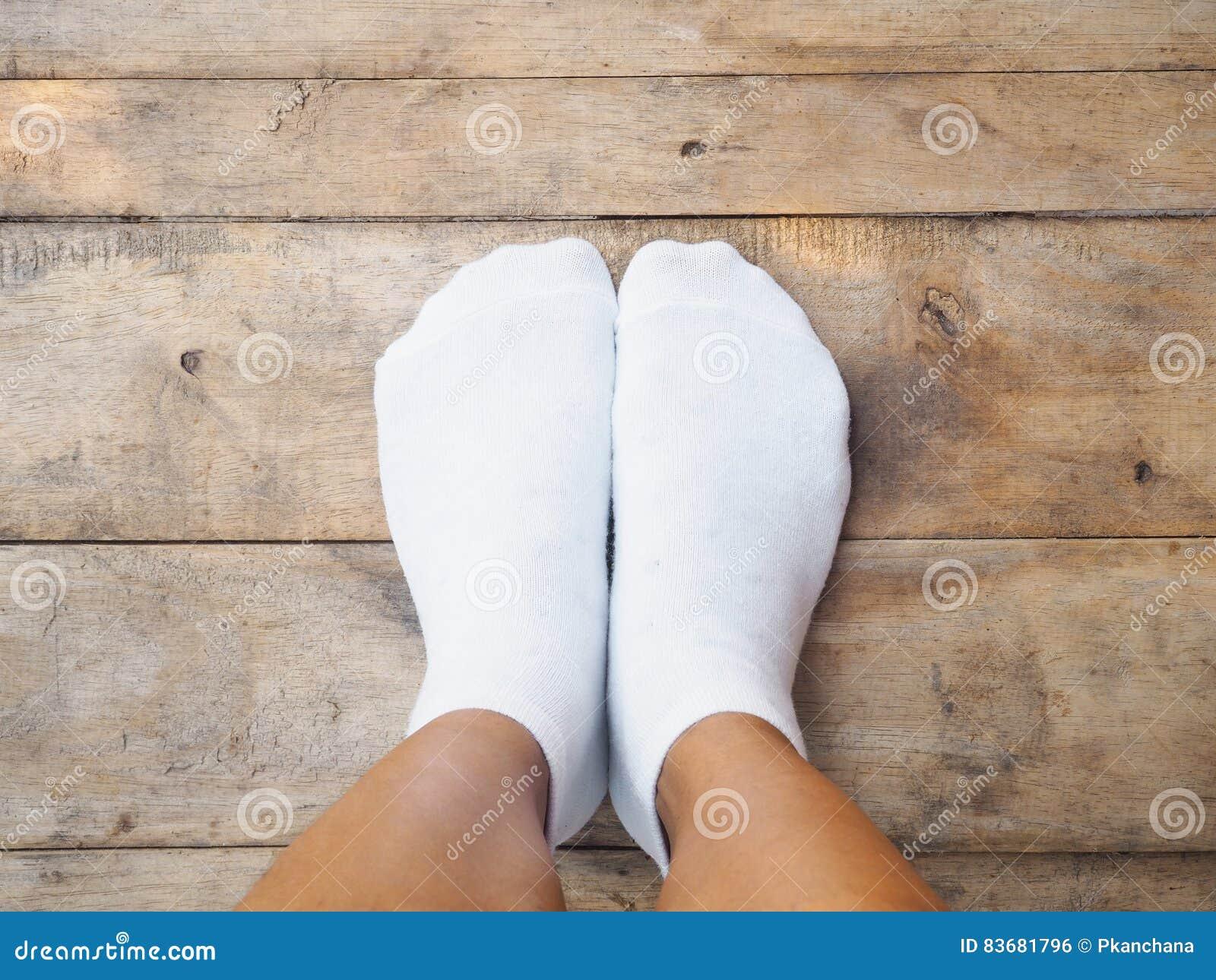Pies que llevan los calcetines blancos en la madera