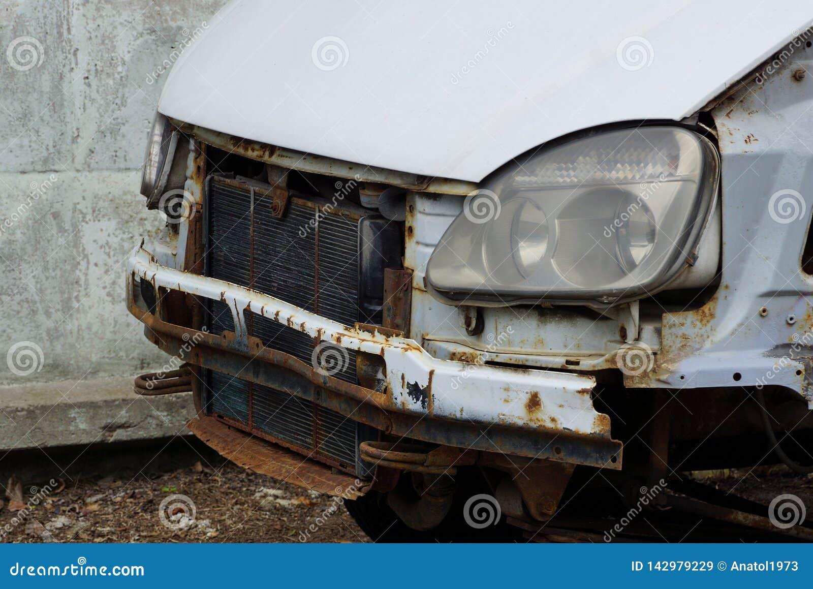 Pieza de un coche estrellado con un radiador y una linterna en la calle