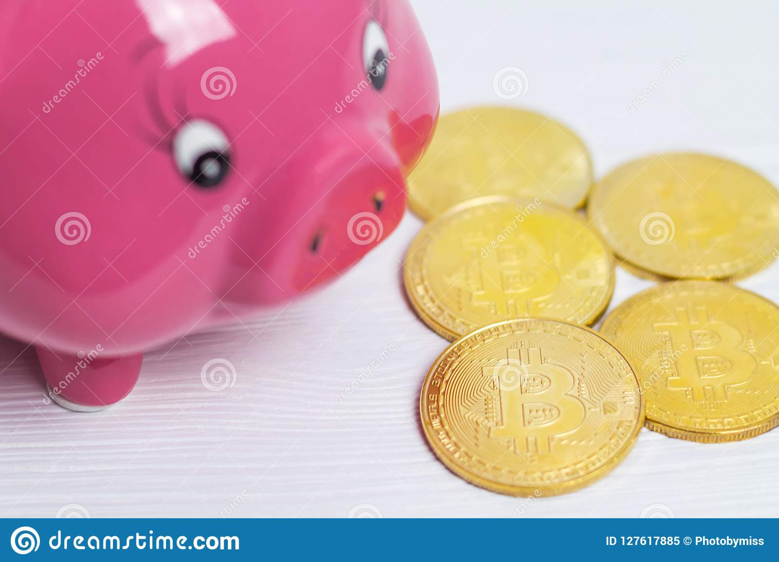 Pig Bank And A Drop Gold Bitcoins On The White Wooden Background, A