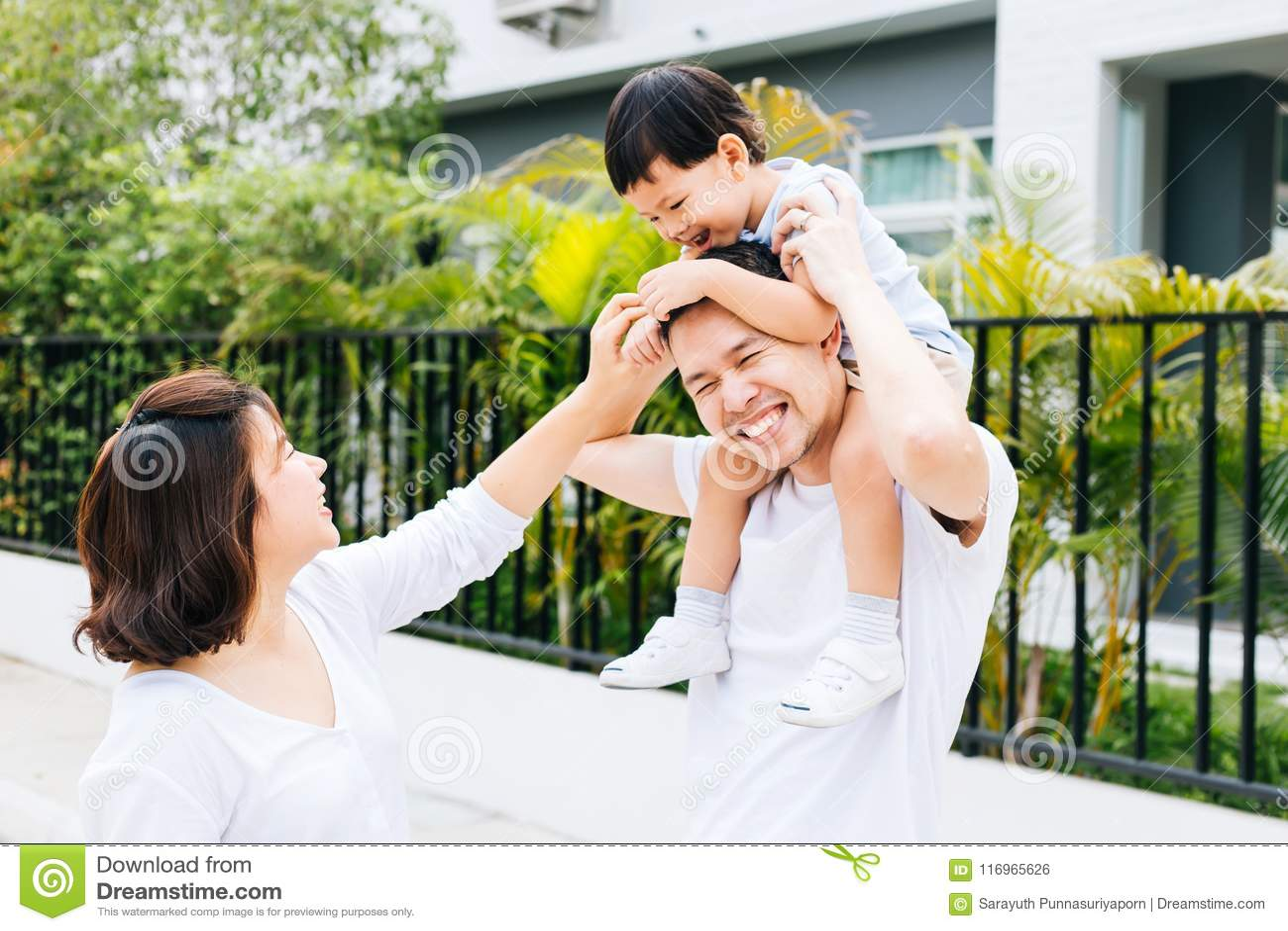 Piggbacking他的儿子的逗人喜爱的亚裔父亲与他的妻子一起在公园 花费时间的激动的家庭与幸福一起