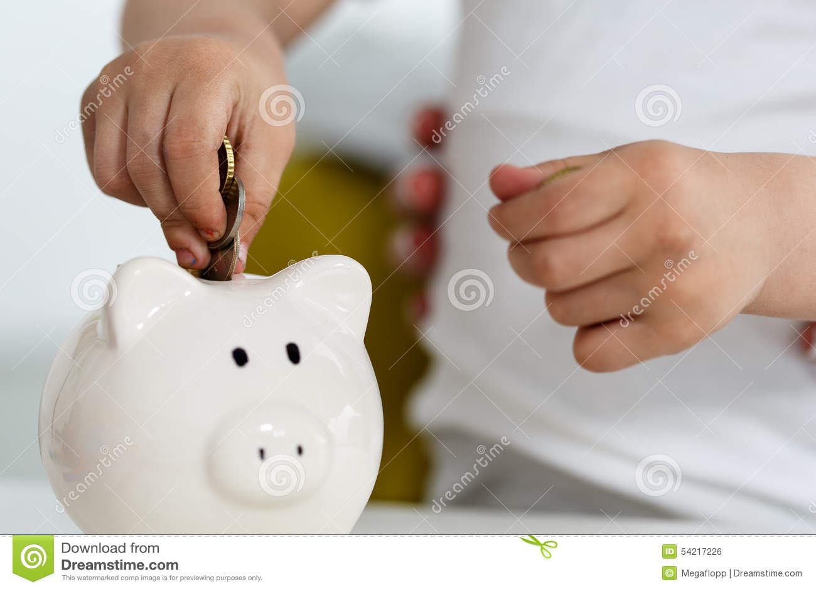 child s hand put into white piggybank money coins  royalty
