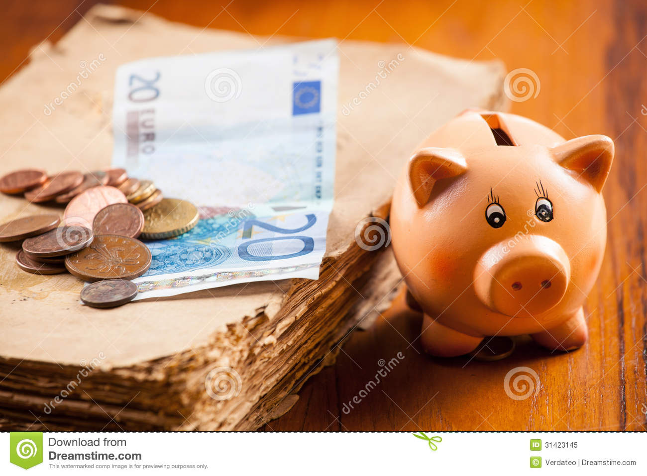 Piggy bank by the old book and euros banknote and pile of coins