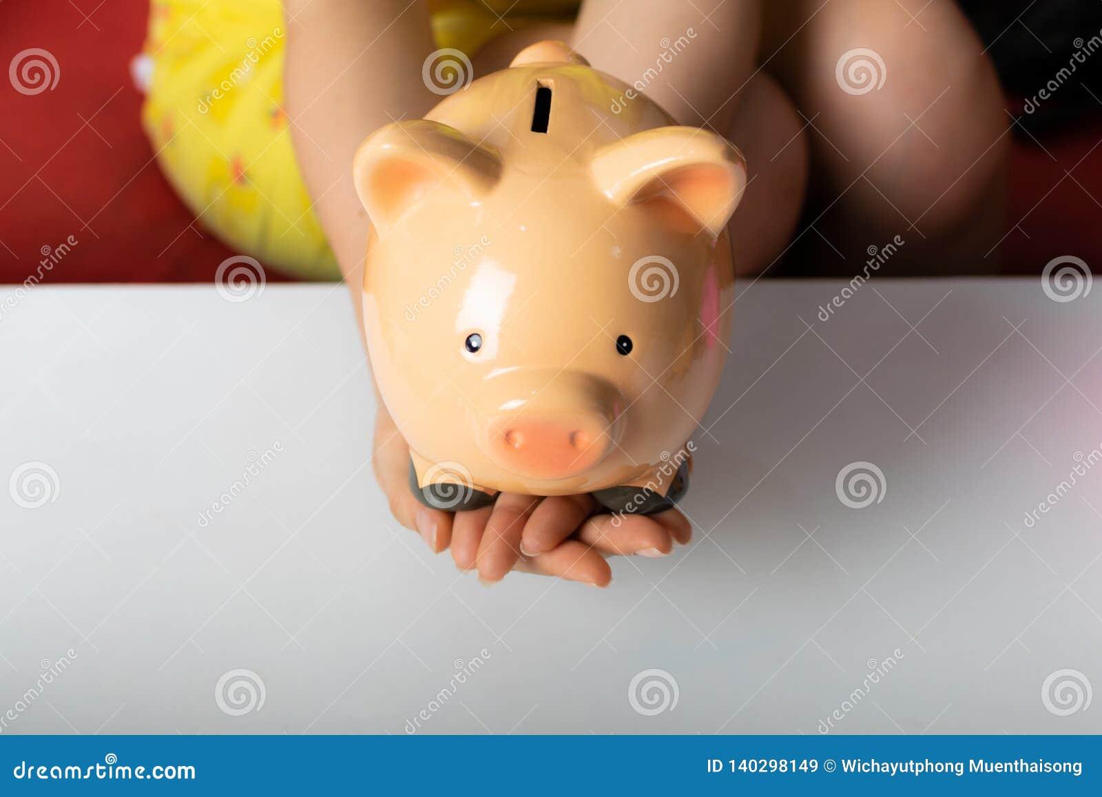 Piggybank del control de la mano de la mujer