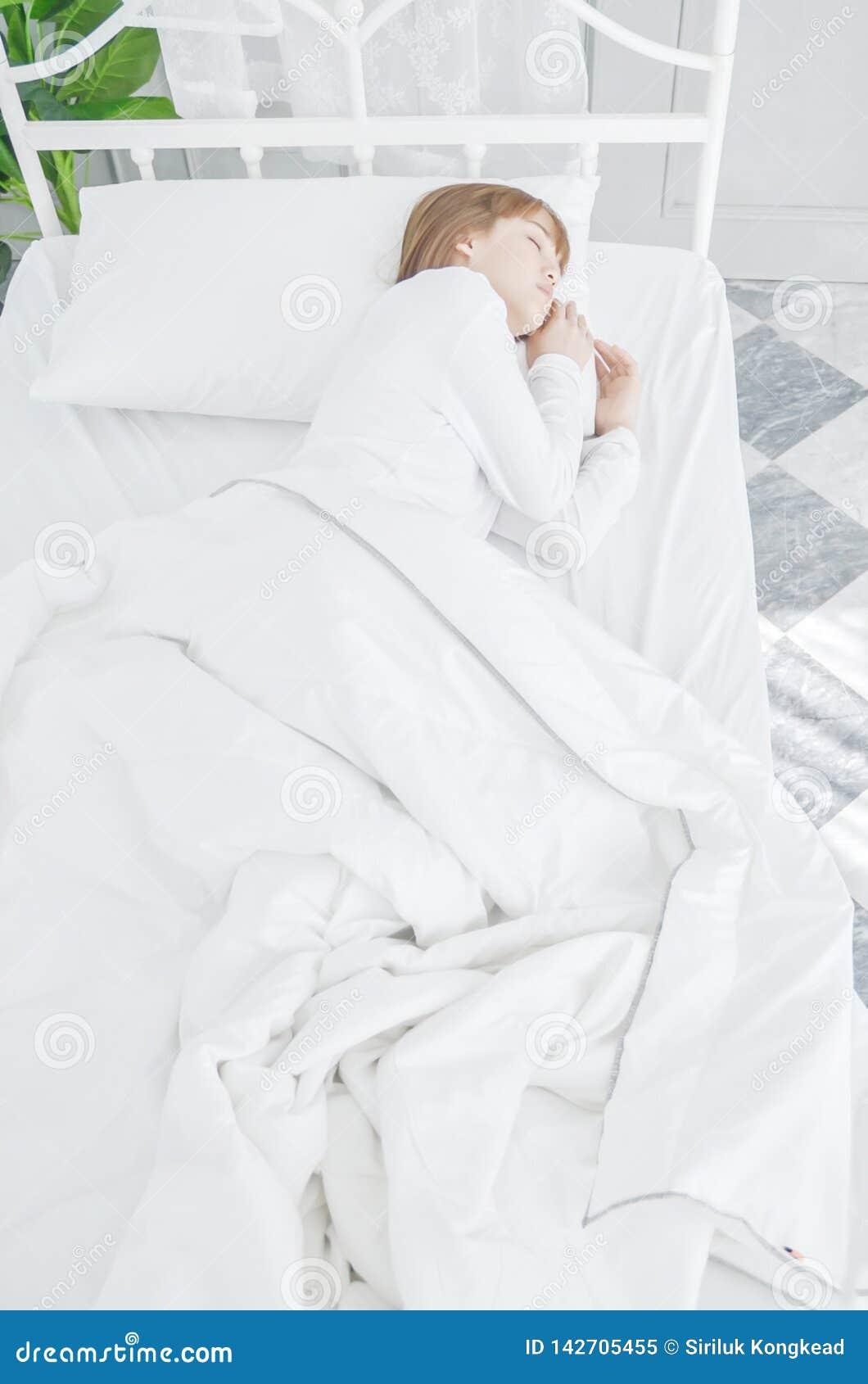 Pijamas blancos de la ropa de mujer en el colchón