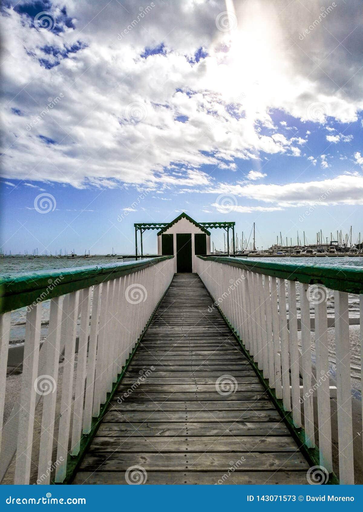 Pijler bij het strand tegen zeegezicht en bewolkte hemel