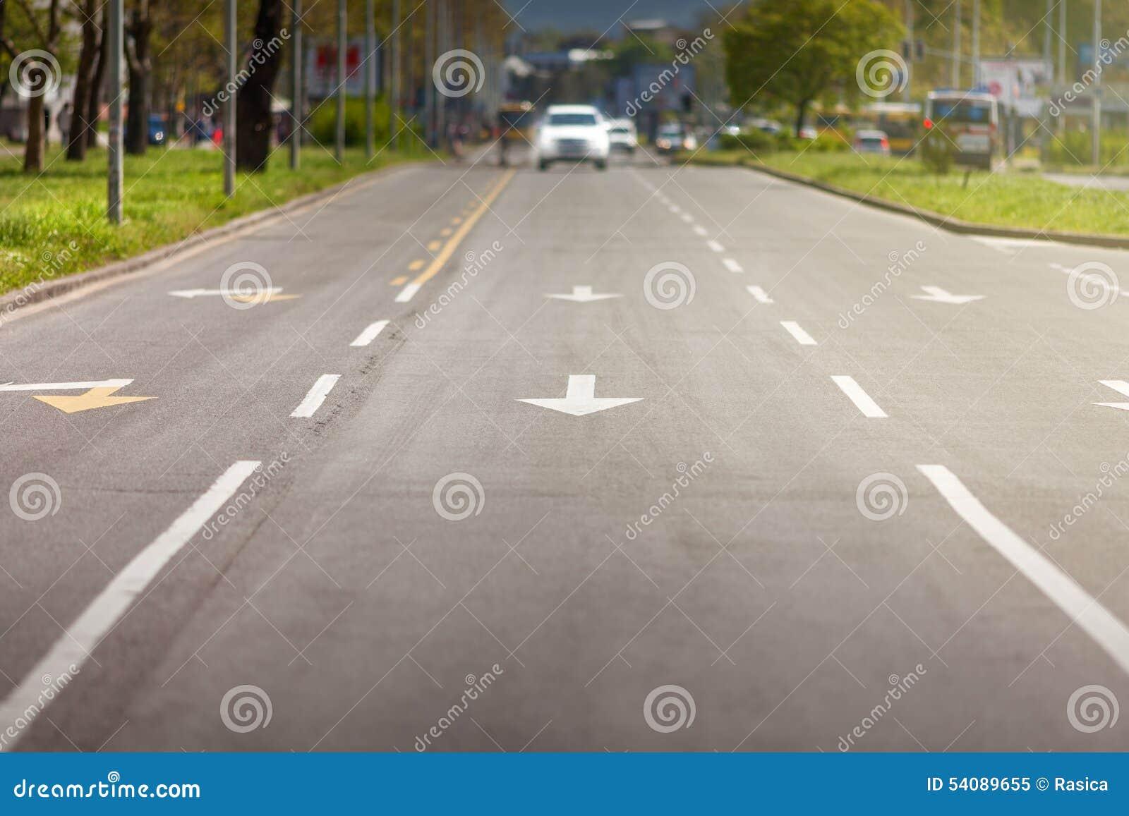 Pijltekens en witte auto op straat