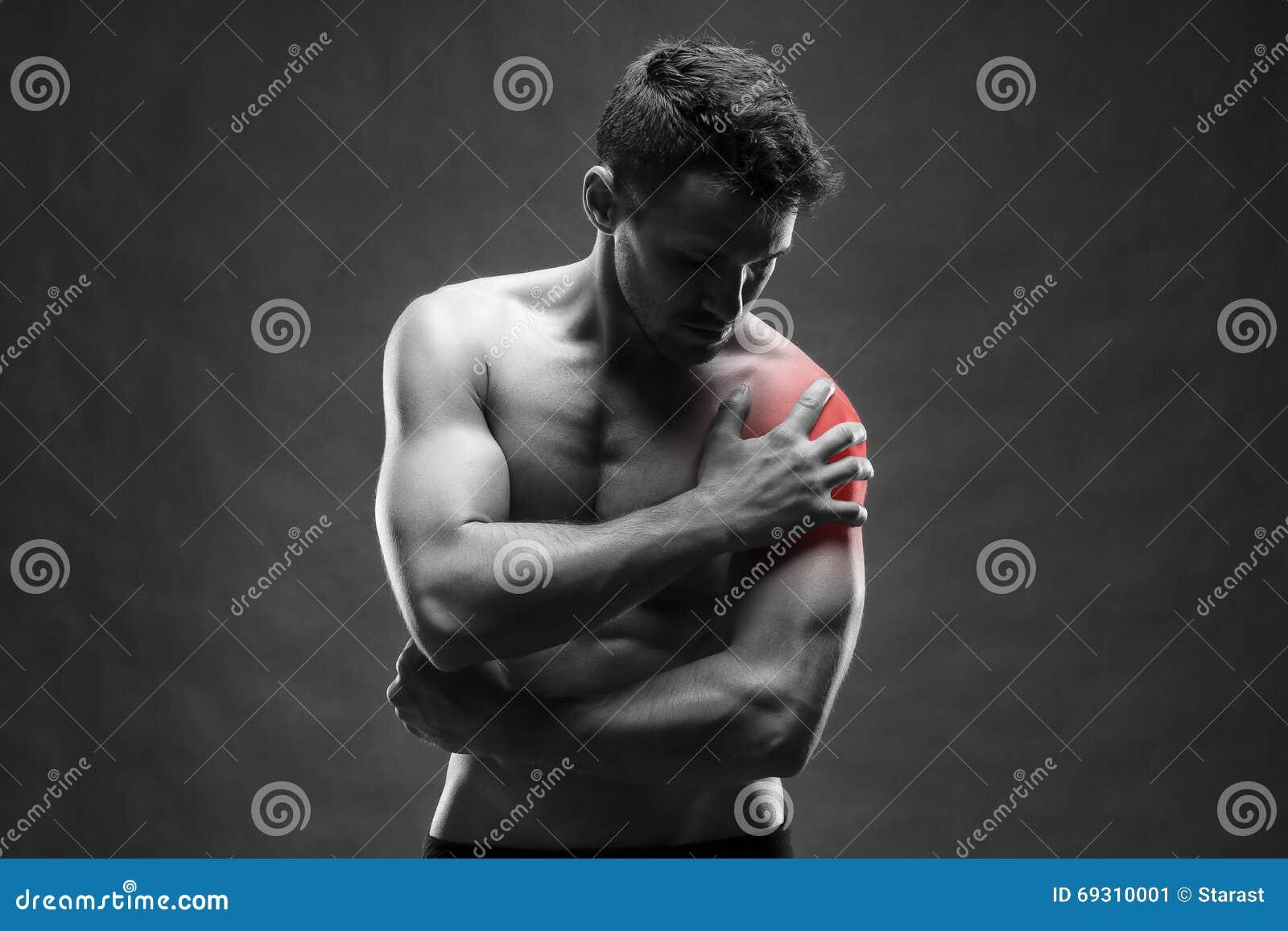 Pijn in de Schouder Spier mannelijk lichaam Het knappe bodybuilder stellen op grijze achtergrond