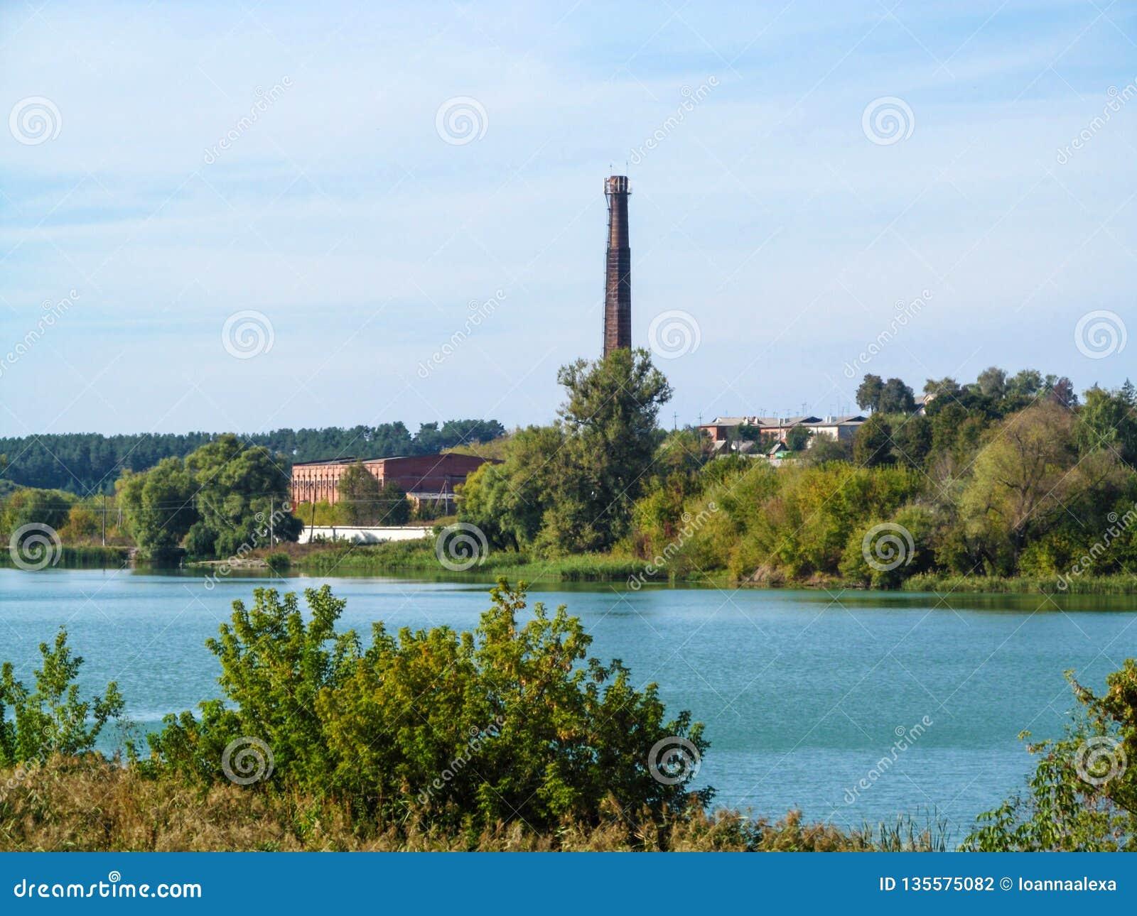 Pijp van vernietigde Ugroidy Sugar Refinery op de bank van het gebied van vijversoumi, de Oekraïne Mooi rustiek industrieel lands