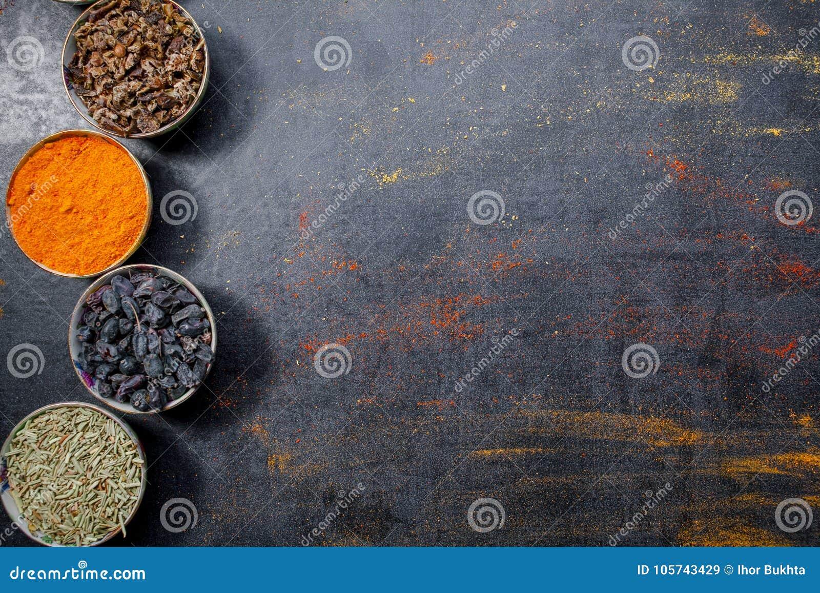 Pikantność kolorowe przyprawy Curry, szafran, turmeric, cynamon i otheron, ciemny betonowy tło Pieprz Wielka kolekcja di