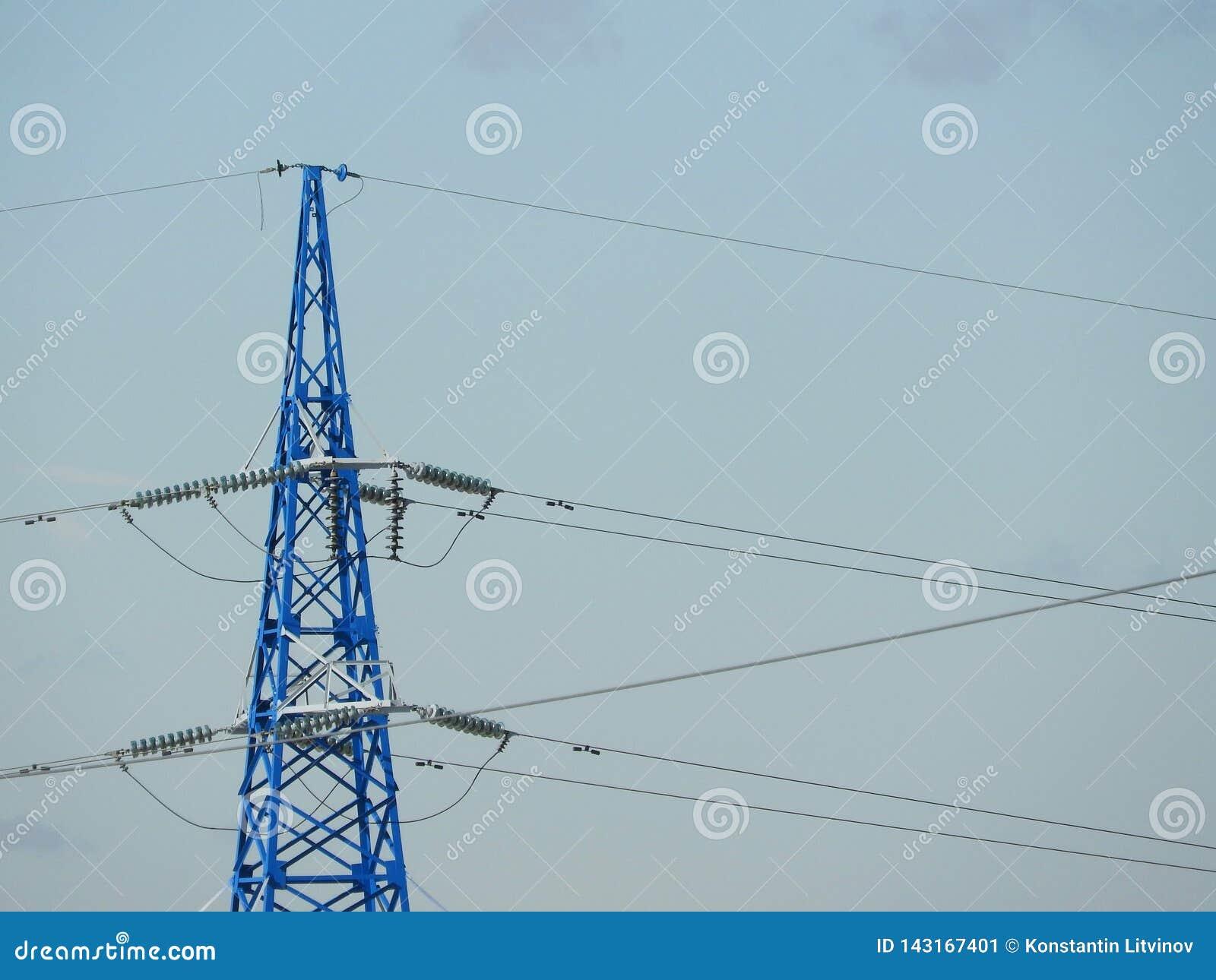 Pilão da eletricidade, torre elétrica da transmissão, contra o céu azul Torre da energia