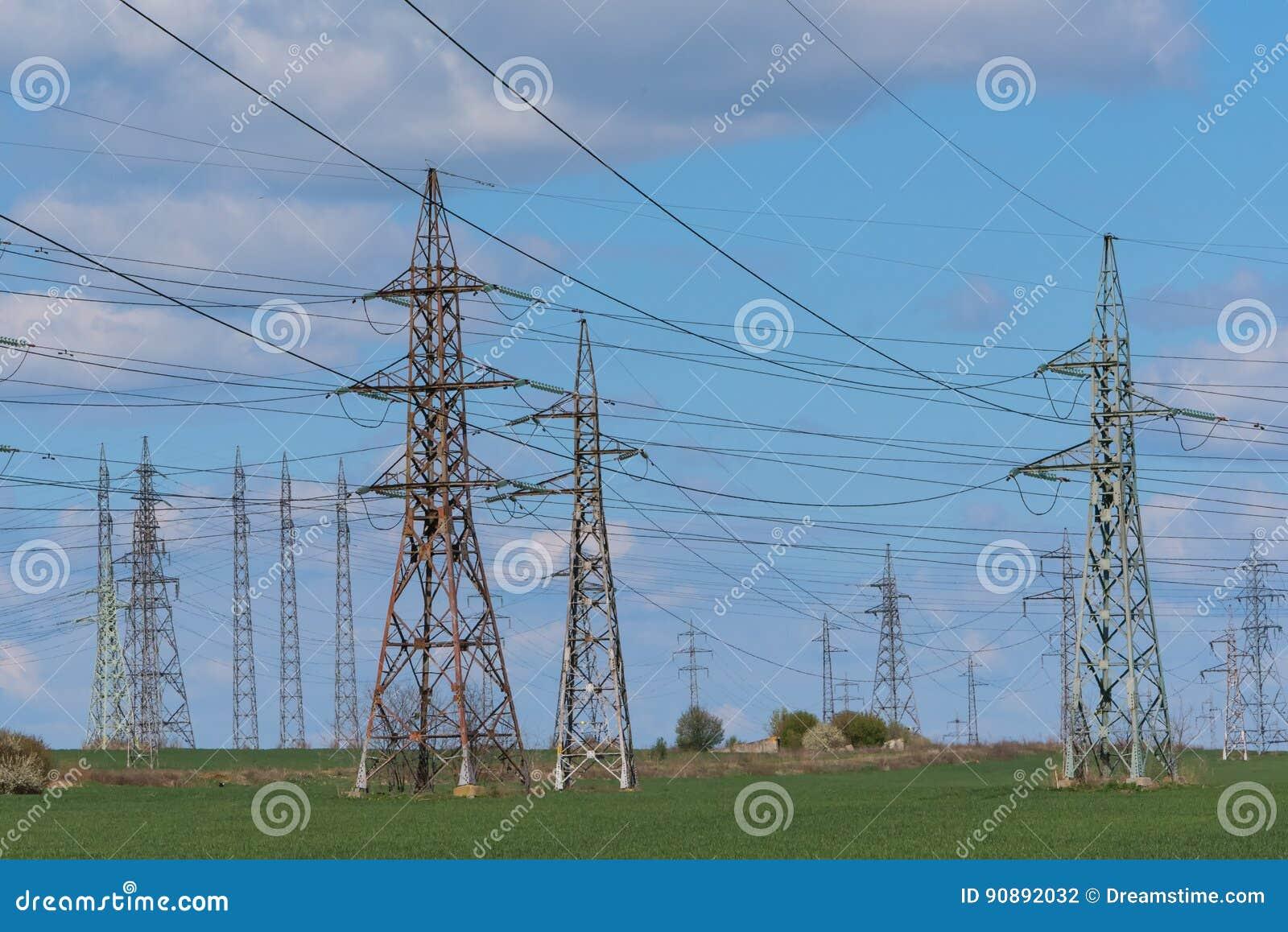Pilón de la electricidad silueteado contra backgrou de la sol del cielo azul