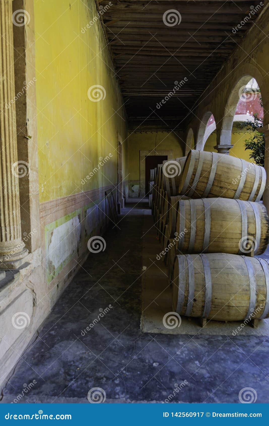 Pila de barriles mezcal en la pared amarilla
