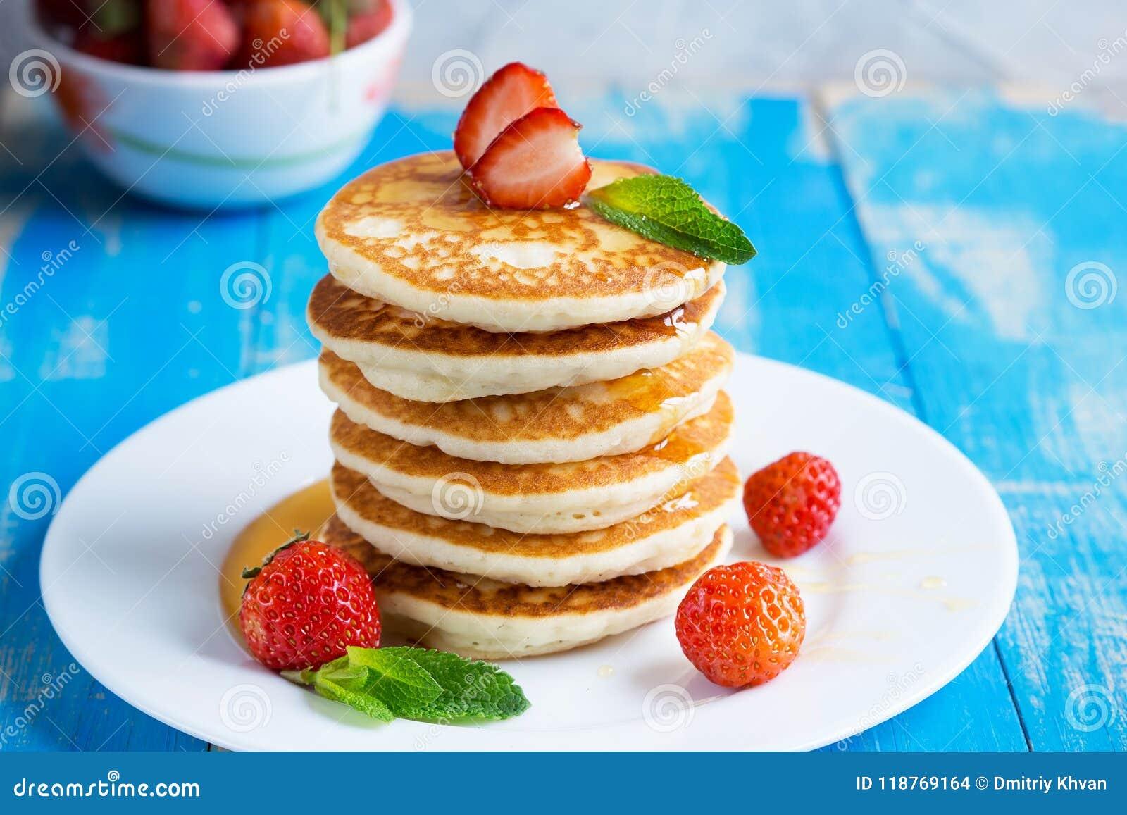 Pila de buñuelos de las crepes con las fresas y la miel en un pl