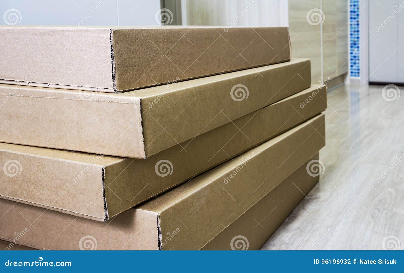 Pila de caja acanalada marrón de los muebles en piso laminado