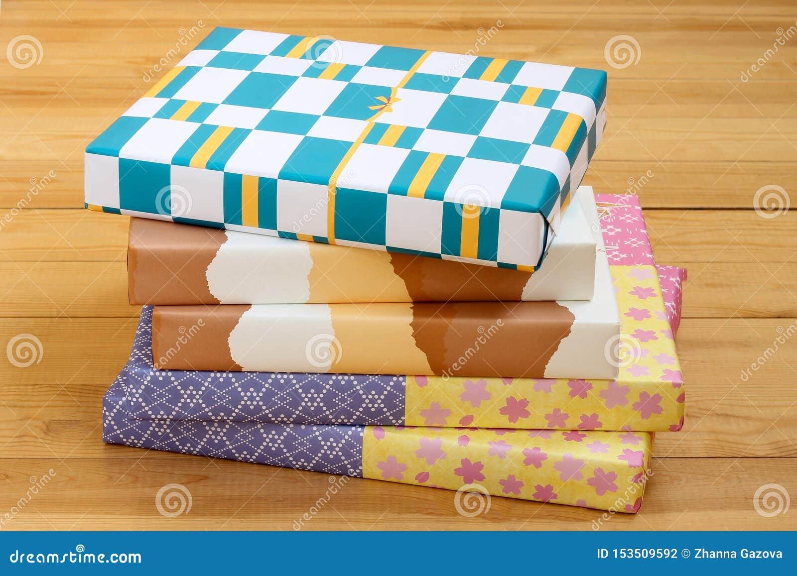 Pila de cajas de color de la cartulina en fondo de madera
