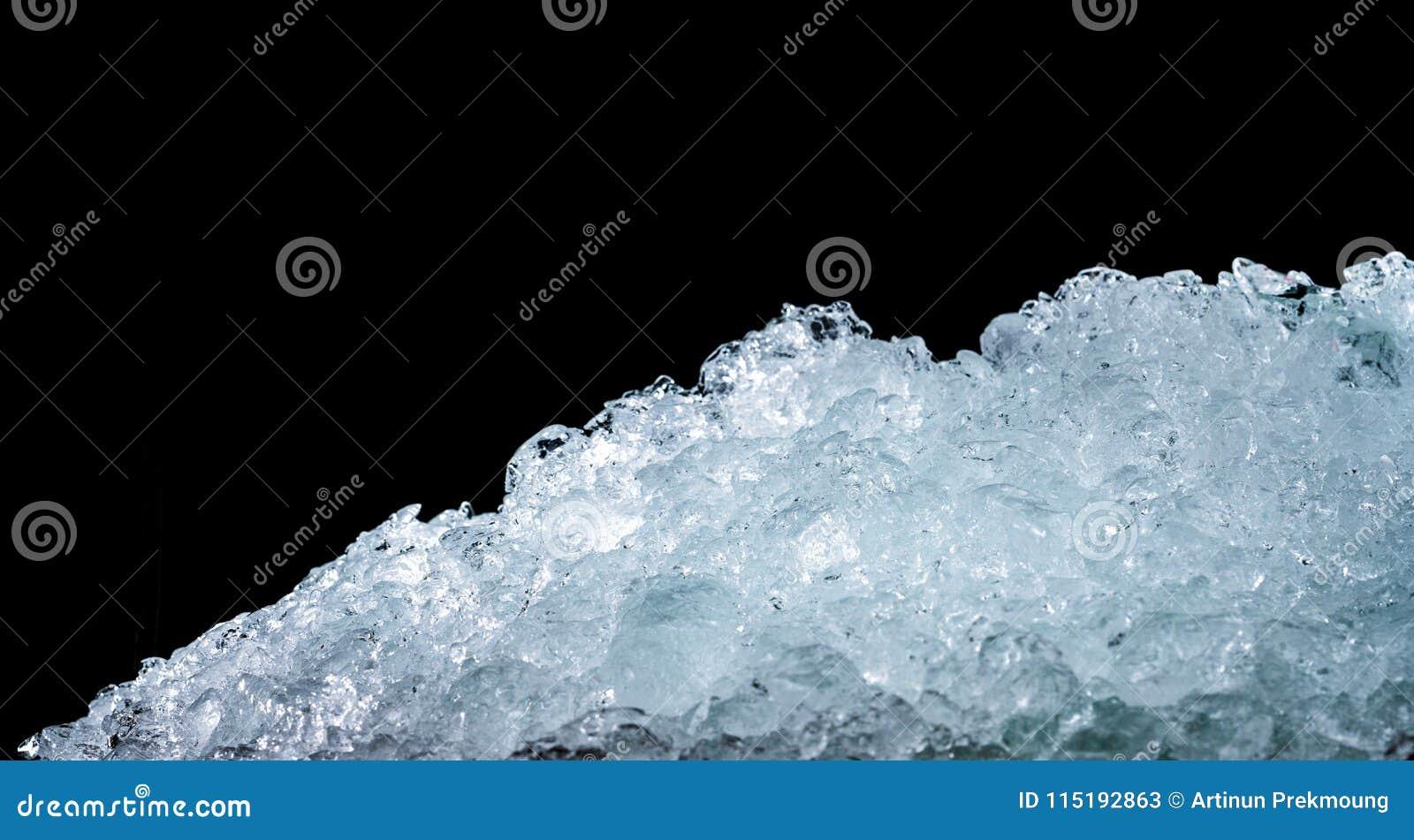 Pila de cubos de hielo machacados en fondo oscuro con el espacio de la copia Primero plano machacado para las bebidas, cerveza, w