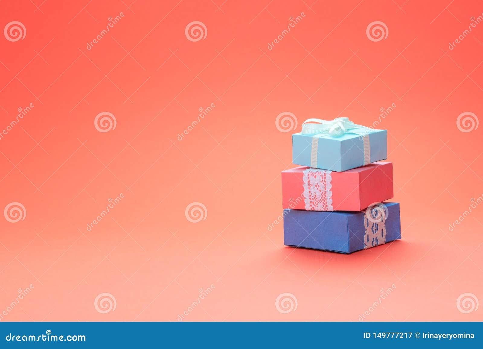 Pila de diversas cajas de regalo de cumpleaños con el cordón en el fondo coralino del color Concepto mínimo, tarjeta de felicitac