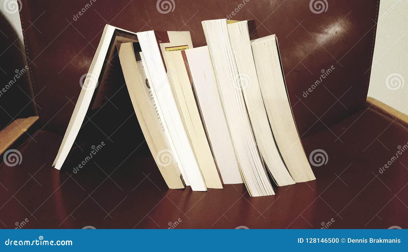 Pila de libro que se inclina en un solo libro