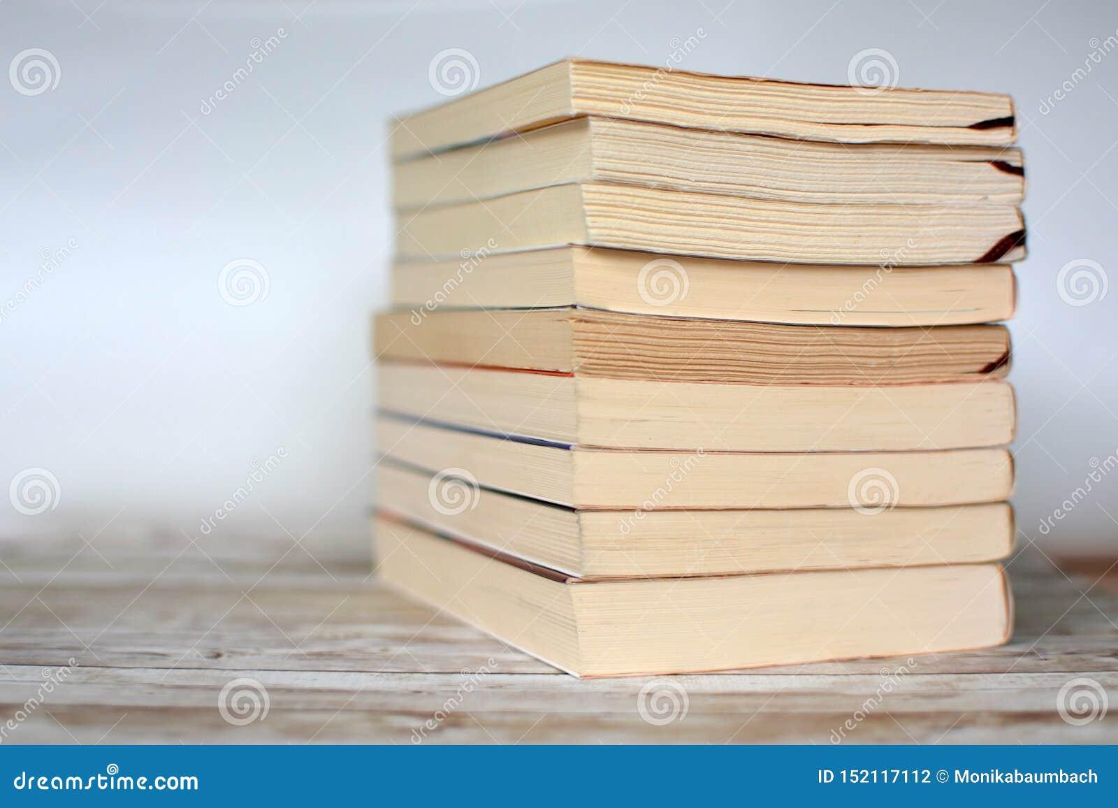 Pila de libros de bolsillo usados viejos amarilleados en el escritorio de madera y el fondo azul claro