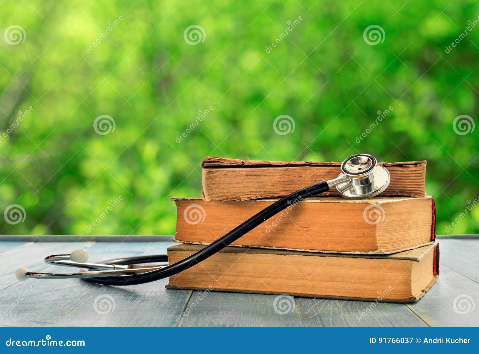 Pila de libros con el estetoscopio en la tabla de madera