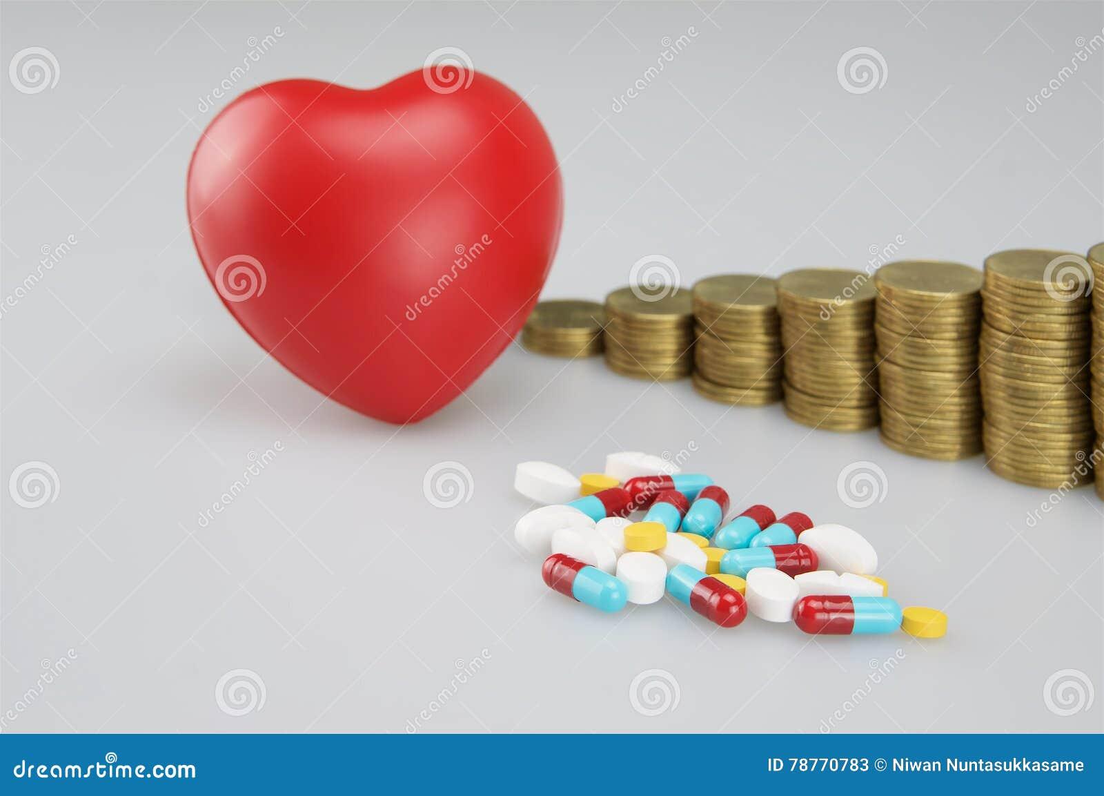 Pila de medicina y de corazón rojo con las monedas de oro