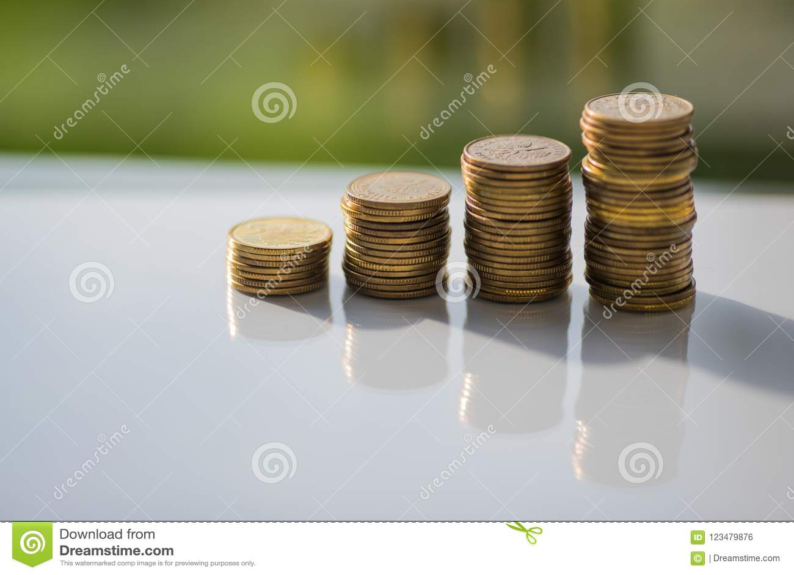 Pila de monedas con reflexiones en la tabla blanca