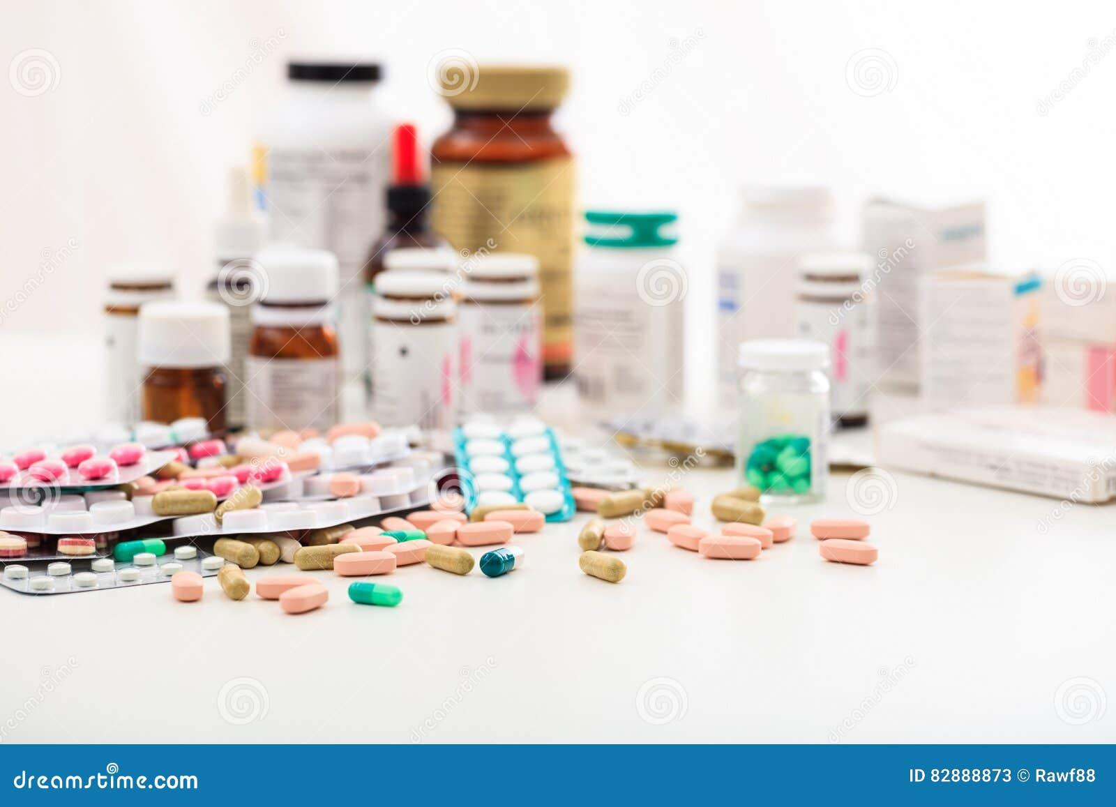 Pila de píldoras y de envases en el fondo blanco