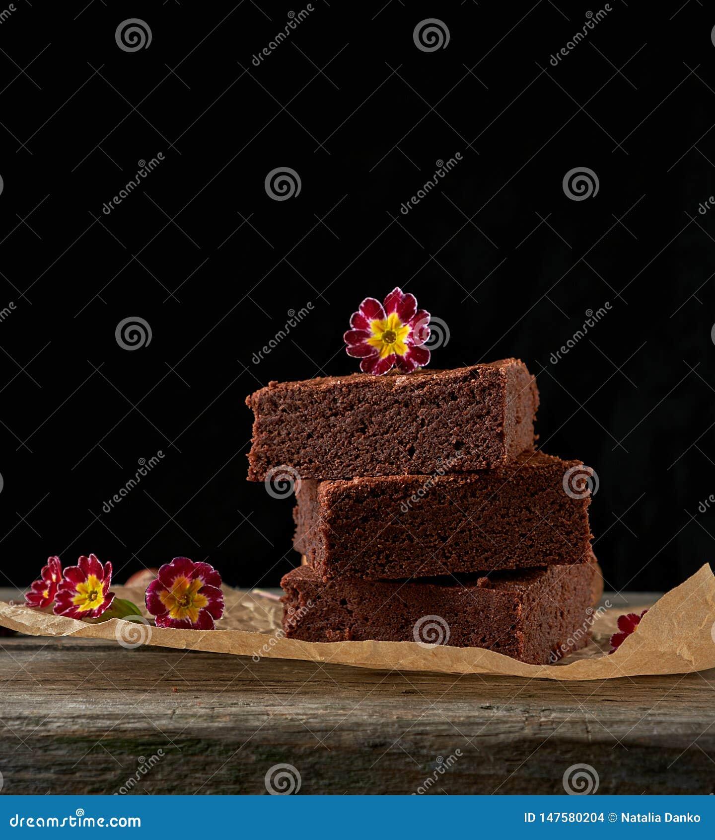 Pila de pedazos cuadrados cocidos de torta del brownie del chocolate