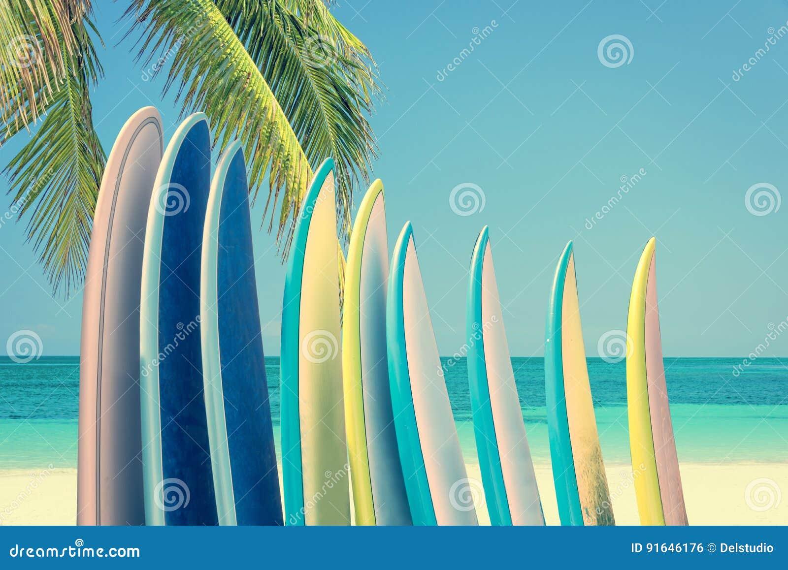 Pila de tablas hawaianas coloridas en una playa tropical por el océano con la palmera, filtro retro del vintage