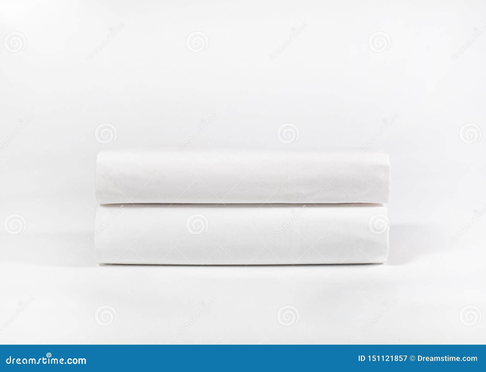Pila de toallas o de hojas blancas del balneario contra el contexto blanco