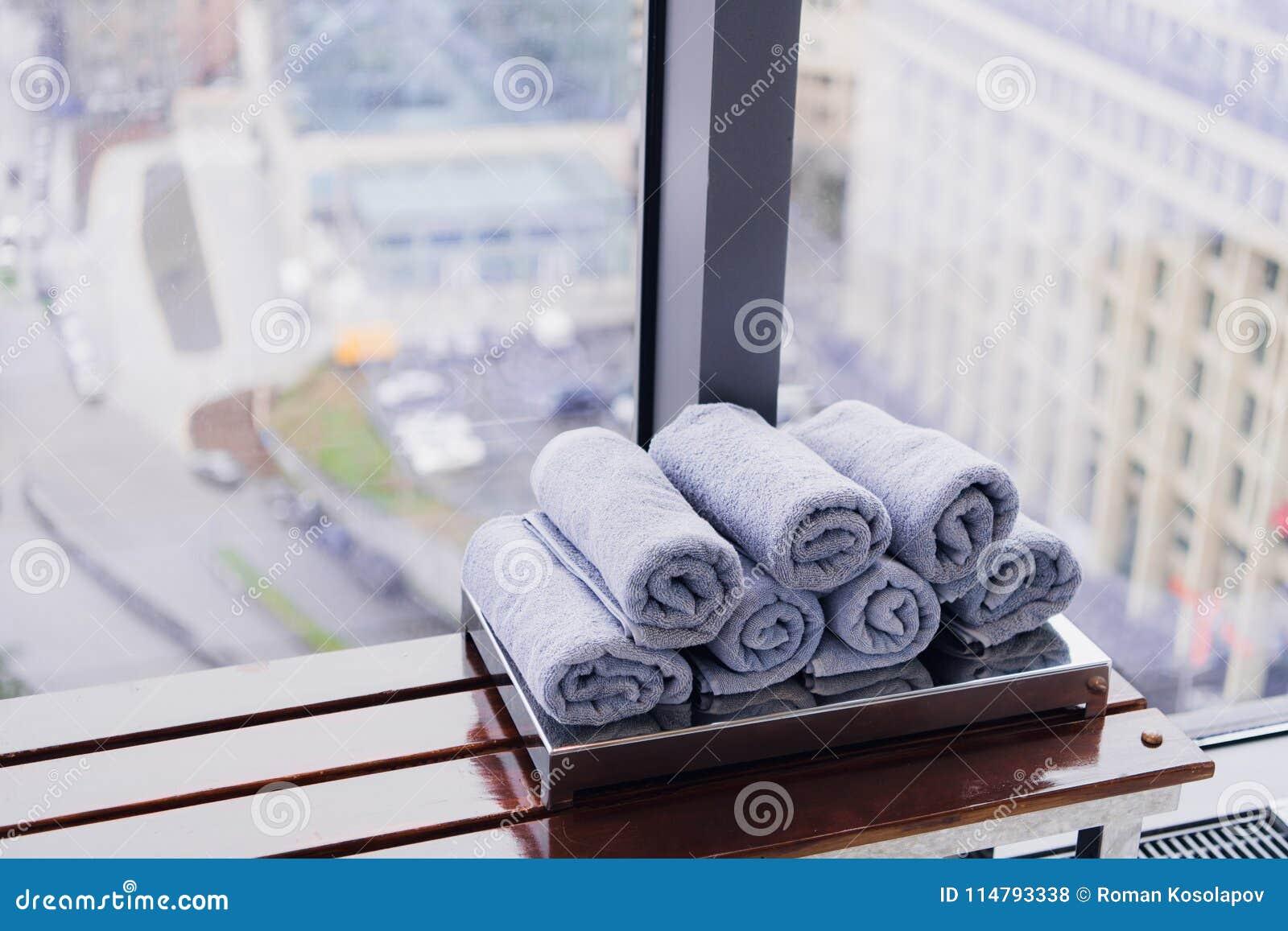 Pila de toallas rodadas en hotel en el gimnasio con la opinión de la ciudad