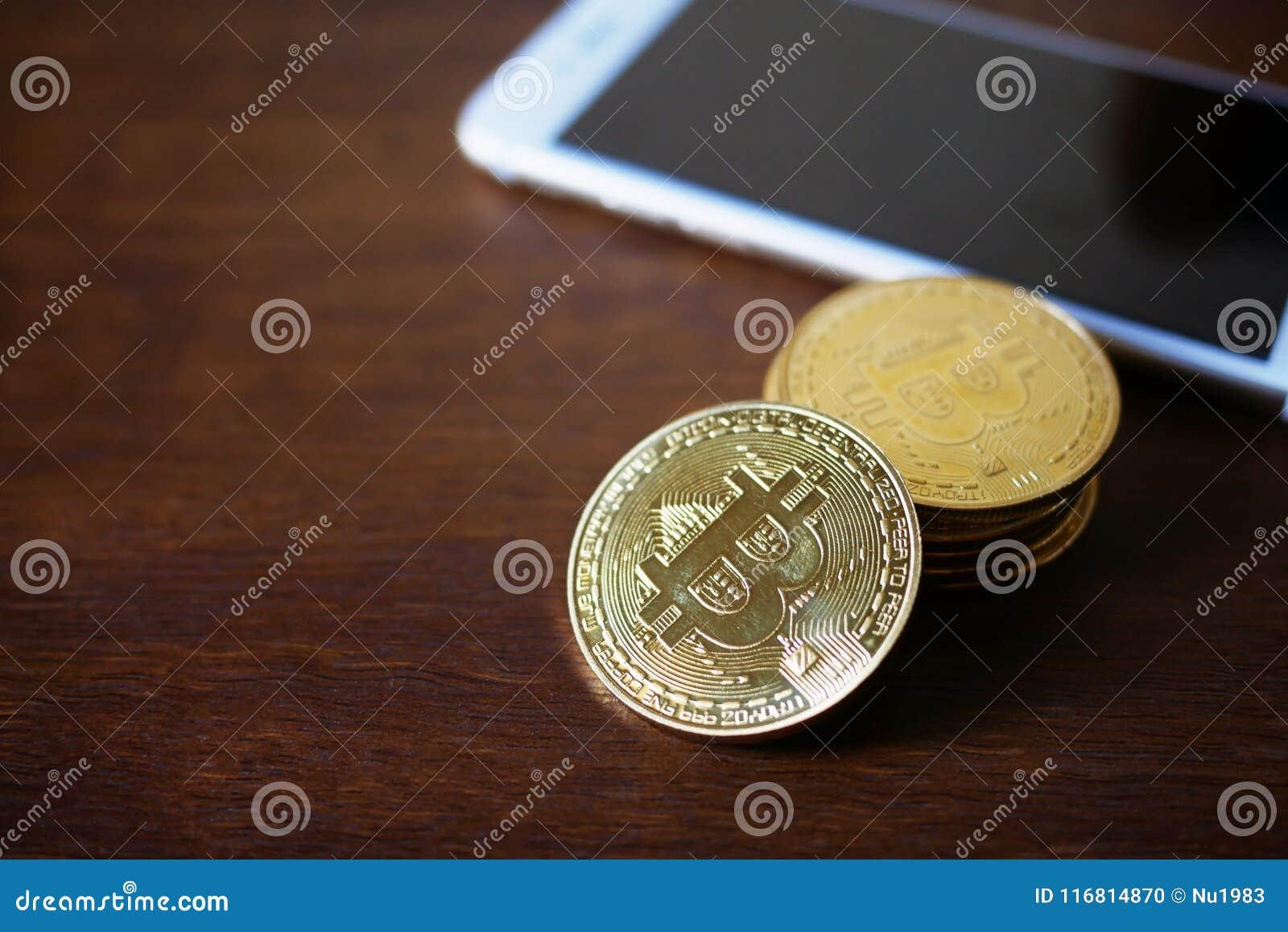 Pila di Bitcoins fisico con valuta virtuale dello smartphone concentrata