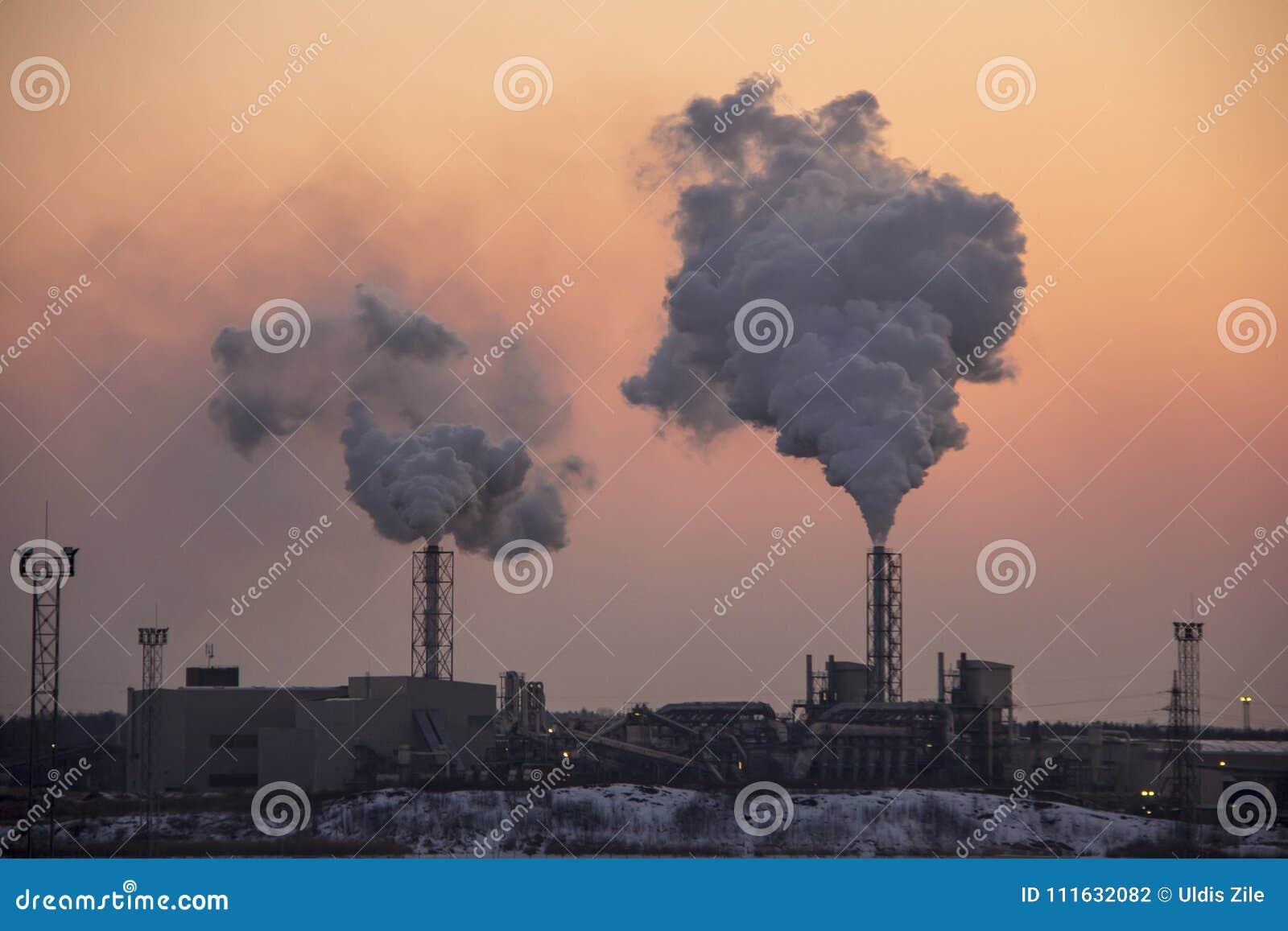 Pila di fumo del camino su alba Inquinamento atmosferico e tema del mutamento climatico
