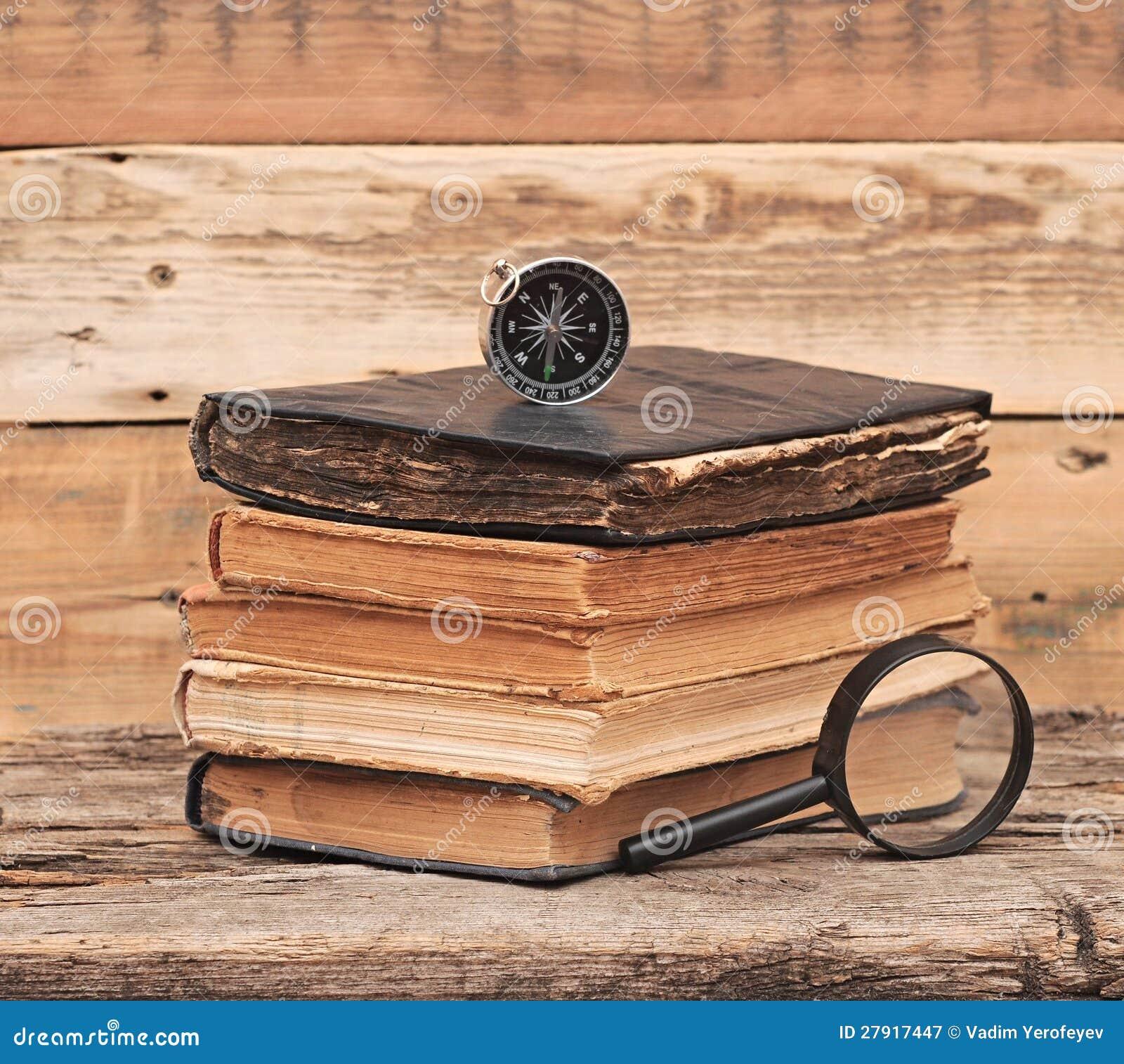 Pila di libri antichi con la lente d 39 ingrandimento - Specchio con lente di ingrandimento ...