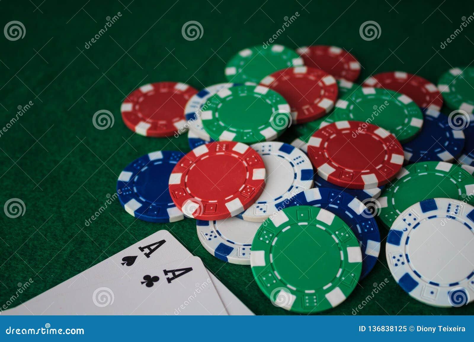 Pila di mazza dei chip e di due assi sulla tavola sulla tela verde Vista di prospettiva