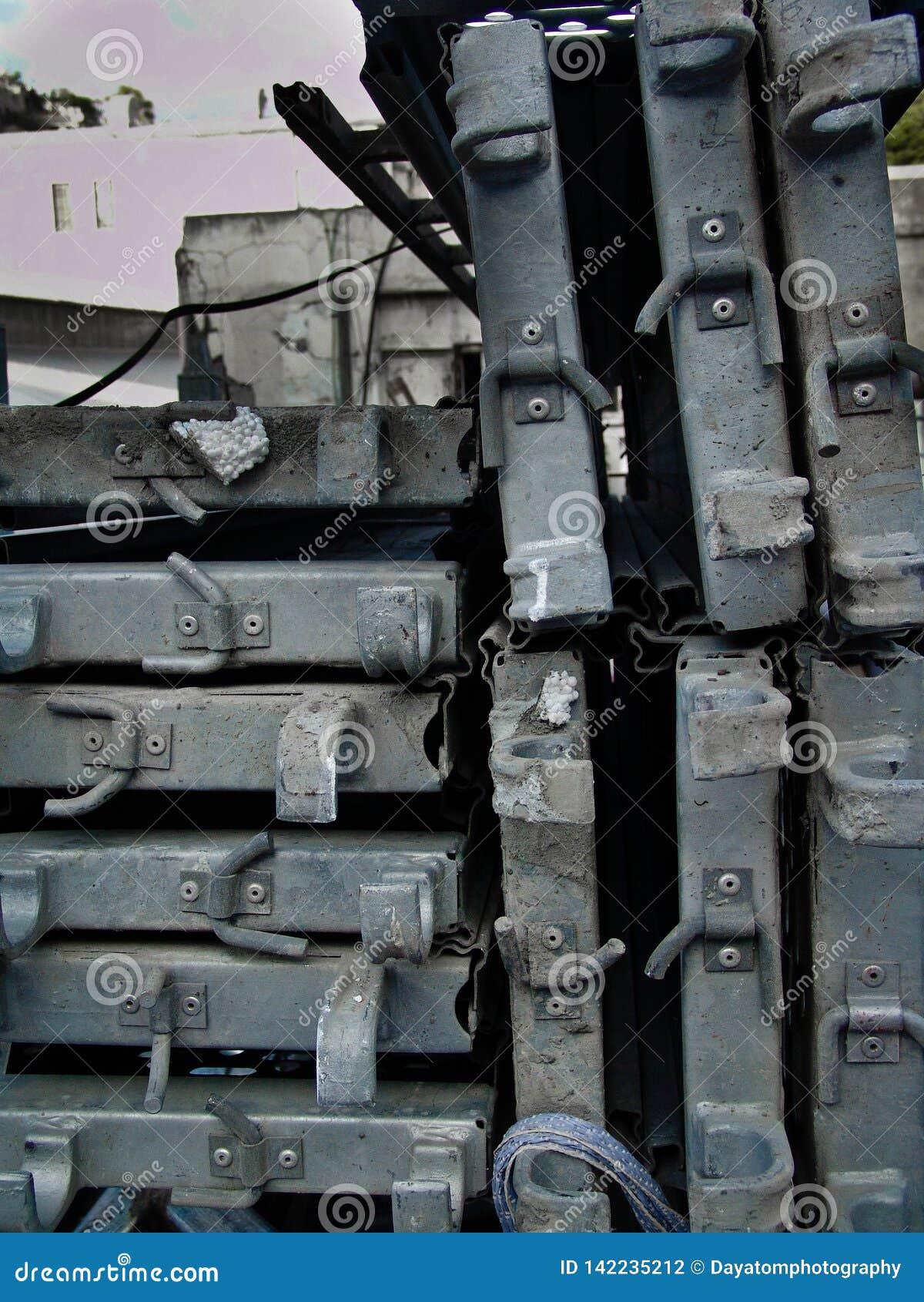 Pila di pezzi del metallo, disposta densamente, ad un cantiere urbano a luce del giorno, in bianco e nero